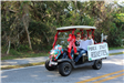 man and woman riding in holiday decorated golf cart