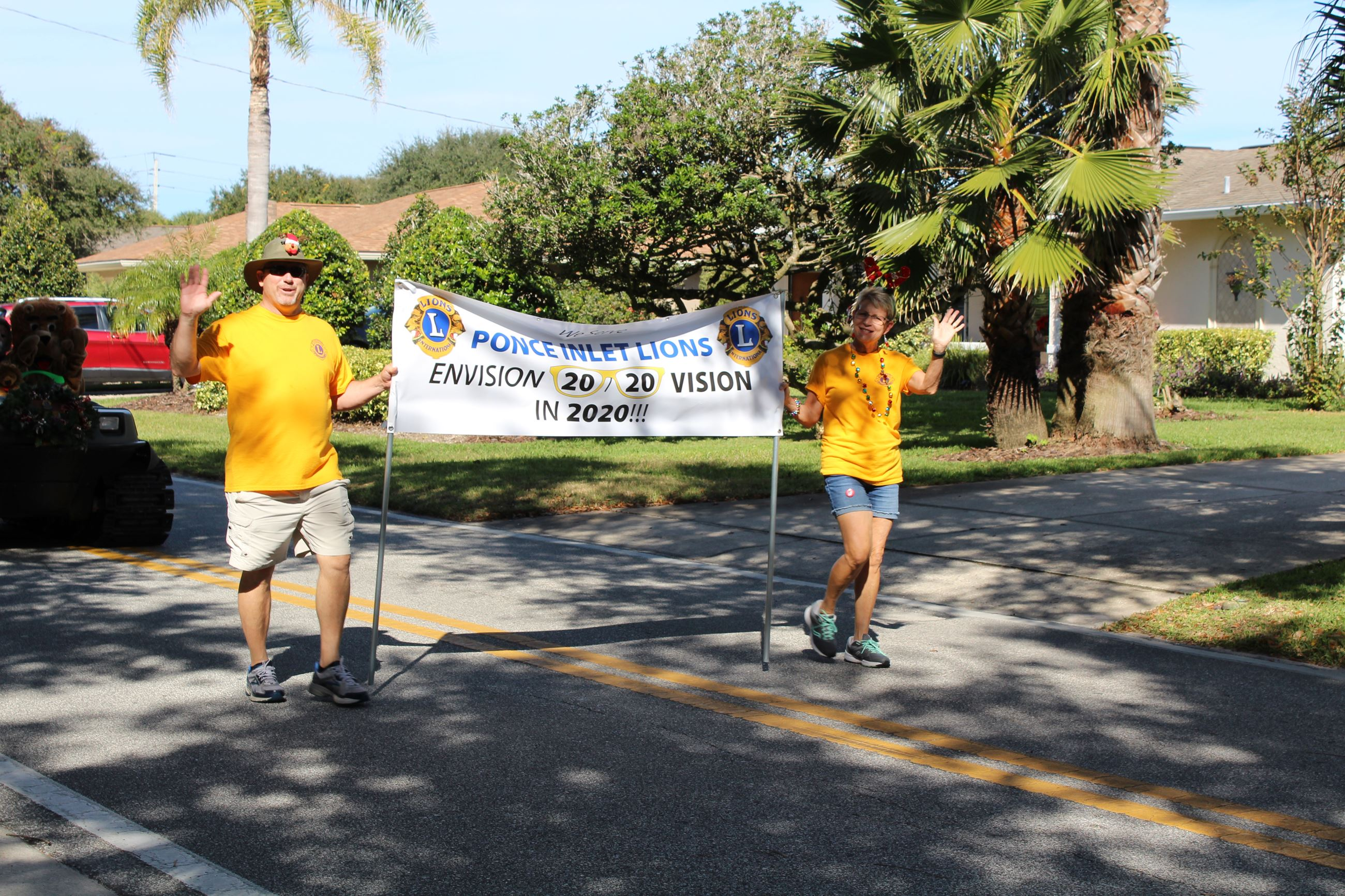 Two adults with yellow tshirts carrying banner